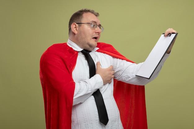 Beeindruckter erwachsener slawischer superheldenmann im roten umhang, der brille und krawatte trägt, hält und betrachtet klemmbrett, das hand auf brust lokalisiert auf olivgrüner wand setzt
