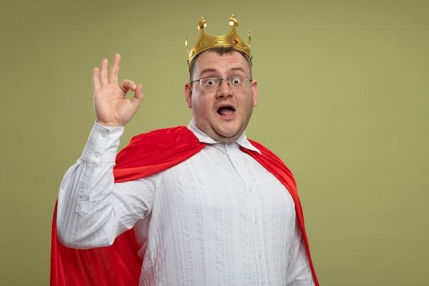 Beeindruckter erwachsener slawischer superheldenmann im roten umhang, der brille und krone trägt, die ok zeichen lokalisiert auf olivgrüner wand mit kopienraum tun