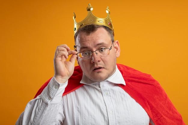 Beeindruckter erwachsener slawischer superheldenmann im roten umhang, der brille und kronengreifbrille trägt, die auf orange wand lokalisiert werden