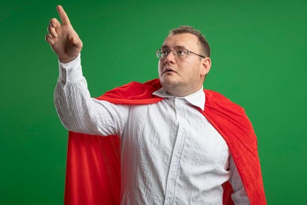 Beeindruckter erwachsener slawischer superheldenmann im roten umhang, der brillen trägt, die lokal auf grünem hintergrund suchen und zeigen