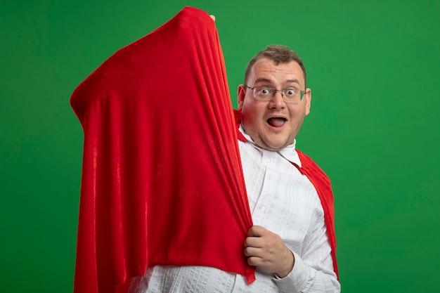 Beeindruckter erwachsener slawischer superheldenmann im roten umhang, der brillen trägt, die umhang betrachten kamera lokalisiert auf grünem hintergrund mit kopienraum