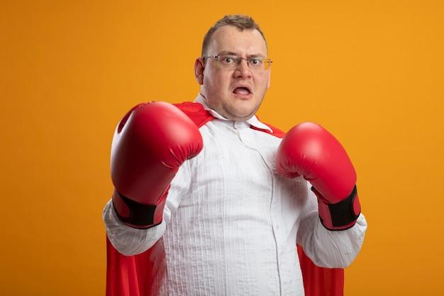 Beeindruckter erwachsener superheldenmann im roten umhang, der brille und kastenhandschuhe trägt, die front betrachten, die hand in der luft halten, die einen anderen nach vorne streckt, isoliert auf orange wand