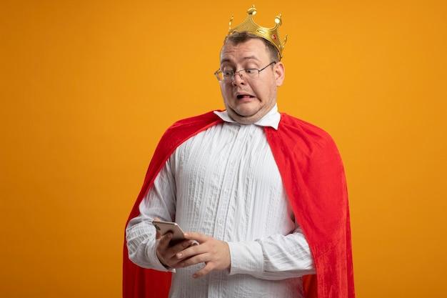 Beeindruckter erwachsener superheldenmann im roten umhang, der brille und krone hält und handy lokalisiert auf orange wand hält