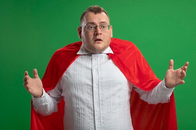 Beeindruckter erwachsener superheldenmann im roten umhang, der brillen trägt, die hände in der luft halten, die seite lokalisiert auf grüner wand betrachten