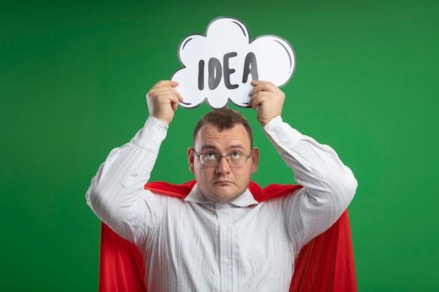 Beeindruckter erwachsener superheldenmann im roten umhang, der die brille hält, die ideenblase über kopf hält, der sie lokalisiert auf grüner wand betrachtet