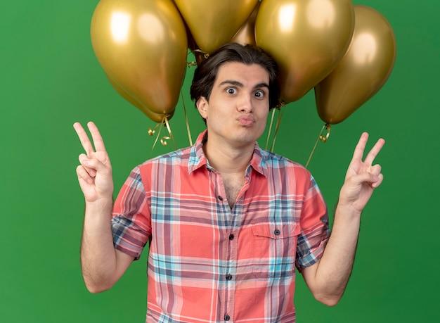 Beeindruckter gutaussehender kaukasier mit geburtstagsmütze steht vor heliumballons und gestikuliert mit zwei händen das sieghandzeichen