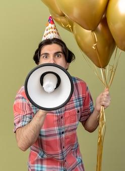 Beeindruckter gutaussehender kaukasischer mann mit geburtstagsmütze hält heliumballons und spricht in lautsprecher
