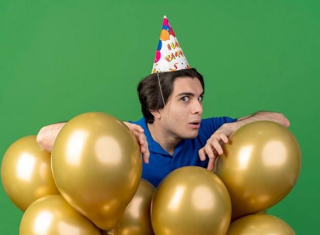 Beeindruckter gutaussehender kaukasischer mann mit geburtstagsmütze steht mit heliumballons