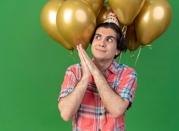Beeindruckter gutaussehender kaukasischer mann mit geburtstagsmütze steht vor heliumballons und hält die hände zusammen und schaut auf die seite