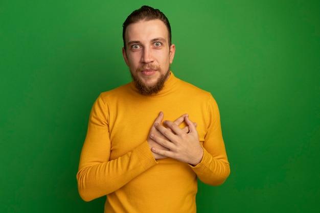 Beeindruckter hübscher blonder mann legt hände auf brust auf grün