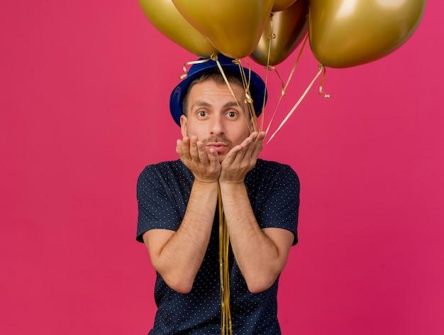 Beeindruckter hübscher kaukasischer mann, der blauen parteihut trägt, hält heliumballons und sendet kuss mit händen, die auf rosa hintergrund mit kopienraum isoliert werden