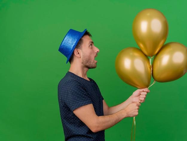 Beeindruckter hübscher mann, der blauen parteihut trägt, steht seitlich und hält heliumballons lokalisiert auf grüner wand mit kopienraum