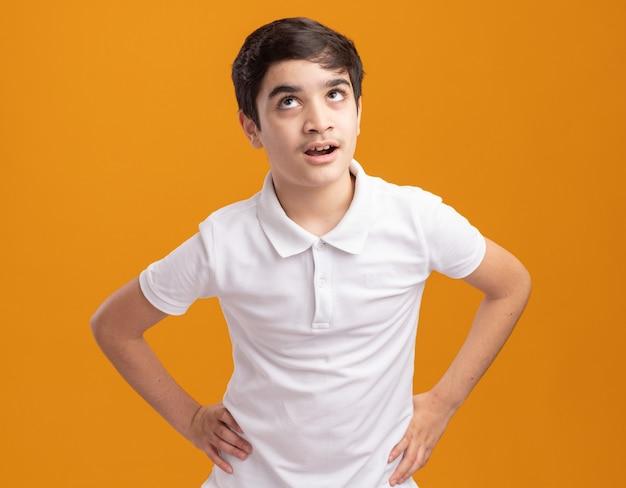 Beeindruckter junge, der die hände an der taille hält und isoliert auf der orangefarbenen wand nach oben schaut