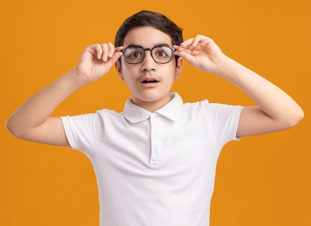 Beeindruckter junge, der eine brille trägt und greift, die gerade isoliert auf der orangefarbenen wand aussieht?