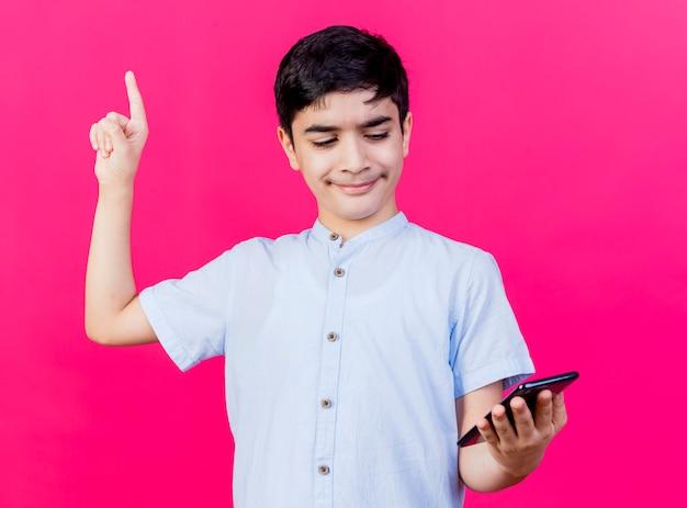 Beeindruckter junge, der handy hält und betrachtet, das lokal auf rosa wand zeigt