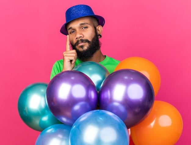 Beeindruckter junger afroamerikaner mit partyhut, der hinter luftballons steht