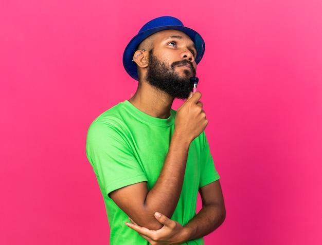 Beeindruckter junger afroamerikaner mit partyhut, der partypfeife isoliert auf rosa wand hält