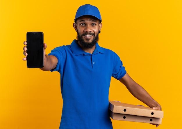 Beeindruckter junger afroamerikanischer lieferbote, der pizzakartons und telefon isoliert auf oranger wand mit kopienraum hält