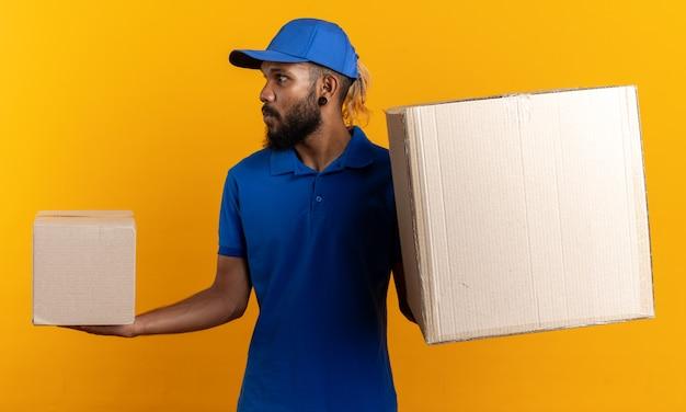 Beeindruckter junger afroamerikanischer liefermann, der pappkartons hält und seitlich isoliert auf oranger wand mit kopierraum schaut