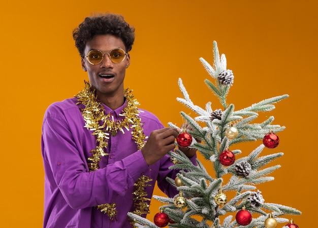 Beeindruckter junger afroamerikanischer mann, der brille mit lametta-girlande um den hals trägt, der nahe verziertem weihnachtsbaum auf orangefarbenem hintergrund steht