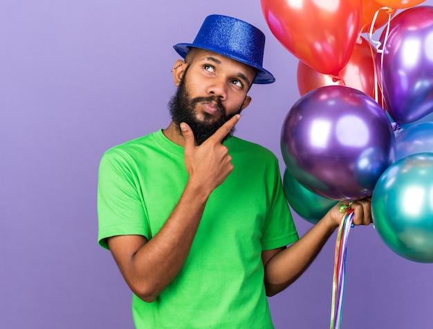 Beeindruckter junger afroamerikanischer mann mit partyhut, der luftballons hält, die hand auf das kinn legen, isoliert auf blauer wand