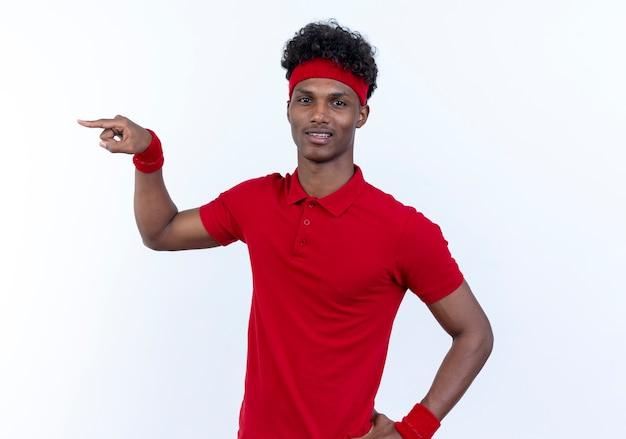 Beeindruckter junger afroamerikanischer, sportlicher mann, der stirnband und armband an der seite trägt und die hand auf die hüfte legt