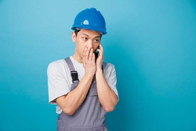 Beeindruckter junger bauarbeiter, der schutzhelm und uniform trägt, die am telefon flüstern, das zur seite schaut