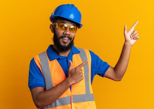 Beeindruckter junger baumeister in schutzbrille, der uniform mit schutzhelm trägt, der auf die seite zeigt, isoliert auf oranger wand mit kopierraum