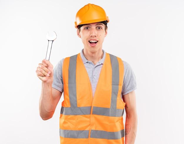 Beeindruckter junger baumeister in uniform mit gabelschlüssel