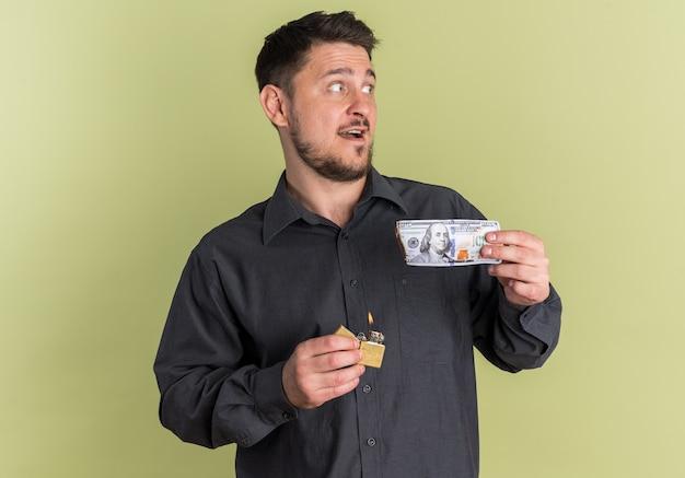 Beeindruckter junger blonder gutaussehender mann, der auf die seite schaut, die feuerzeug und halb verbrannten dollar hält