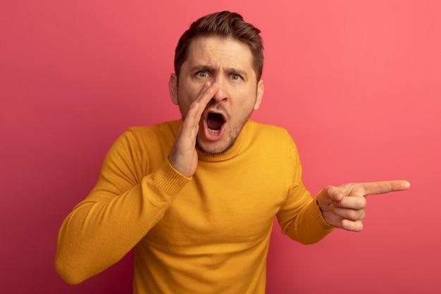 Beeindruckter junger blonder gutaussehender mann, der die hand in der nähe des mundes hält und auf das seitliche flüstern zeigt
