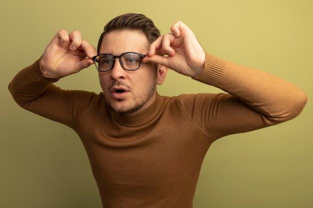 Beeindruckter junger blonder gutaussehender mann, der eine brille trägt und ergreift, die auf die seite schaut
