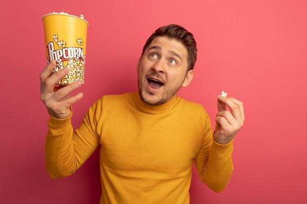 Beeindruckter junger blonder gutaussehender mann, der einen eimer mit popcorn und popcornstück nach oben hält