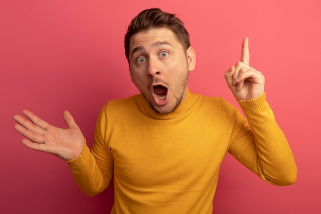 Beeindruckter junger blonder gutaussehender mann, der leere hand zeigt, die isoliert auf rosa wand zeigt