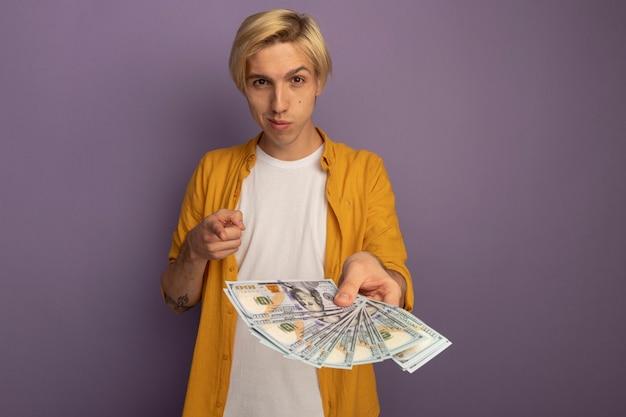 Beeindruckter junger blonder kerl, der gelbes t-shirt trägt, das sie geste zeigt und bargeld heraushält