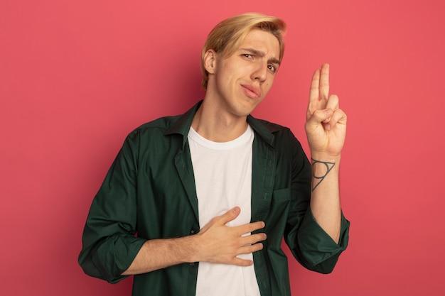 Beeindruckter junger blonder kerl, der grünes t-shirt trägt, zeigt auf hand auf bauch lokalisiert auf rosa