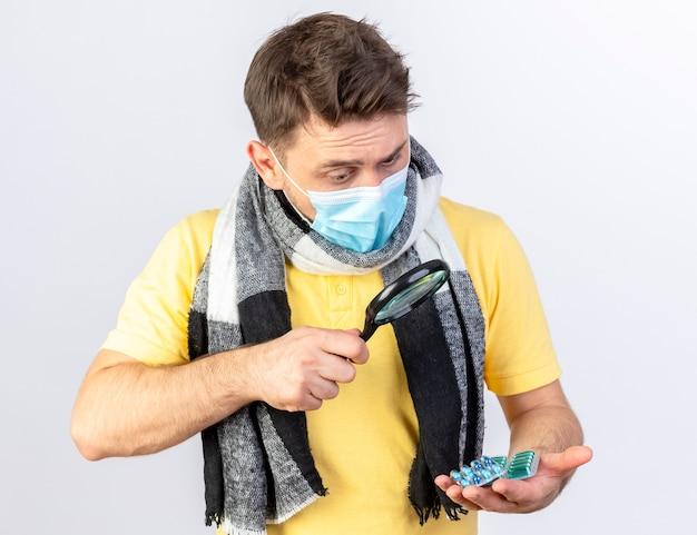 Beeindruckter junger blonder kranker mann, der medizinische maske und schal trägt, betrachtet packungen von medizinischen pillen durch lupe lokalisiert auf weißer wand