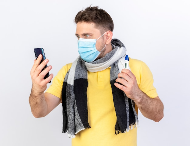 Beeindruckter junger blonder kranker slawischer mann, der medizinische maske und schal trägt, schaut auf telefon und hält thermometer lokalisiert auf weißer wand mit kopienraum