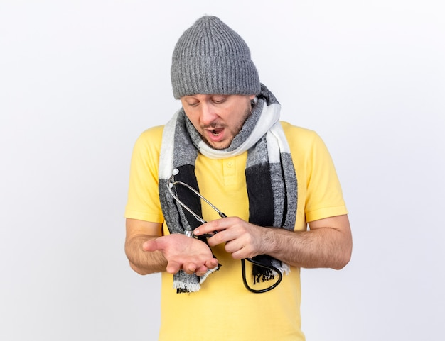 Beeindruckter junger blonder kranker slawischer mann, der wintermütze und schal trägt