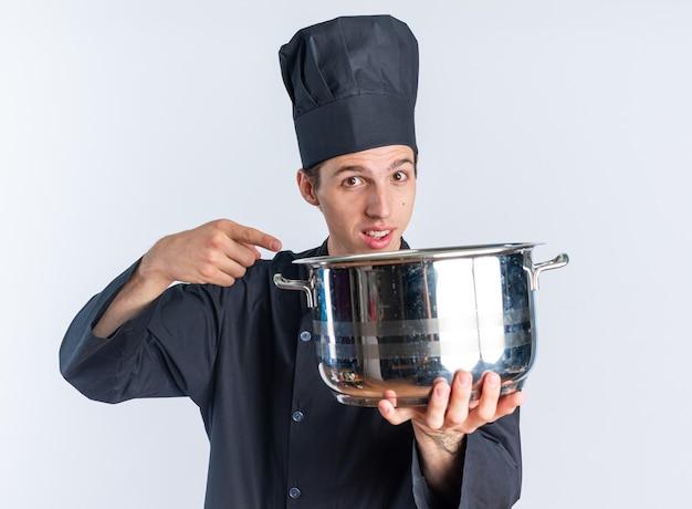 Beeindruckter junger blonder männlicher koch in kochuniform und mütze, der den topf in richtung der kamera ausstreckt, die auf die kamera zeigt, die auf der weißen wand isoliert ist
