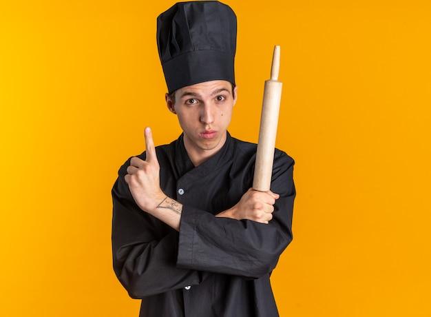 Beeindruckter junger blonder männlicher koch in kochuniform und mütze, der die hände gekreuzt hält und nudelholz hält und auf die kamera schaut, die isoliert auf orangefarbener wand mit kopierraum zeigt