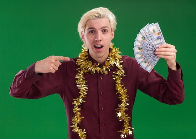 Beeindruckter junger blonder mann, der eine brille mit lametta-girlande um den hals trägt und auf geld zeigt, das auf grüner wand lokalisiert wird