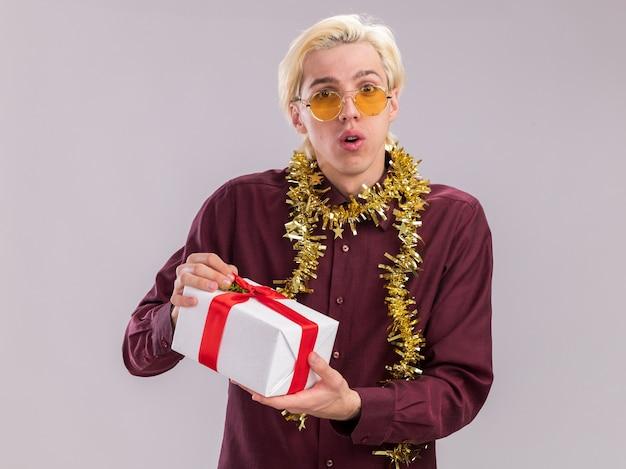 Beeindruckter junger blonder mann, der eine brille mit lametta-girlande um den hals trägt und ein geschenkpaket hält, das auf die kamera isoliert auf weißem hintergrund blickt