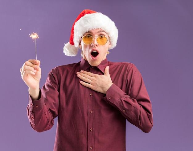 Beeindruckter junger blonder mann, der weihnachtsmütze und brille hält, die feiertagswunderkerze betrachten, die kamera hält hand auf brust lokalisiert auf lila hintergrund hält