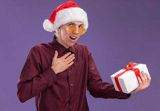 Beeindruckter junger blonder mann, der weihnachtsmütze und brille hält, die geschenkverpackung tut, die dankesgeste lokalisiert auf lila wand tut