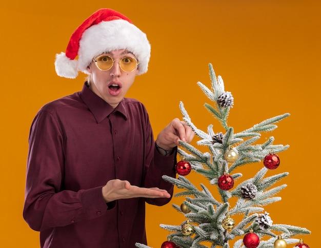 Beeindruckter junger blonder mann mit weihnachtsmütze und brille, der in der nähe des geschmückten weihnachtsbaums steht und weihnachtskugel hält, die auf den baum zeigt und die kamera auf orangefarbenem hintergrund betrachtet