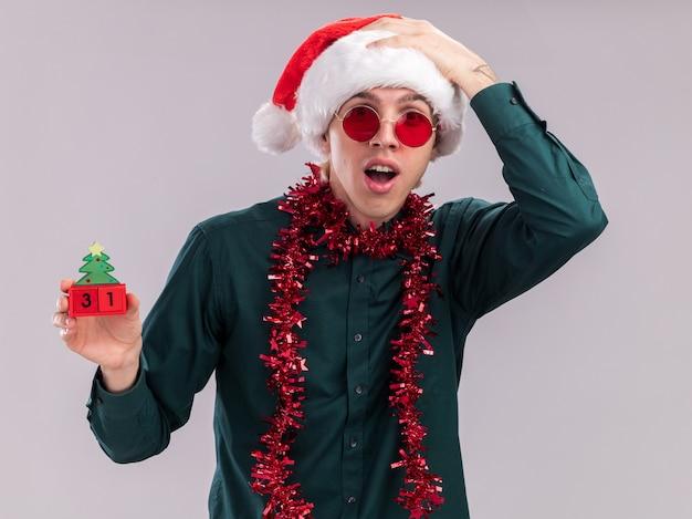 Beeindruckter junger blonder mann mit weihnachtsmütze und brille mit lametta-girlande um den hals, der ein weihnachtsbaumspielzeug mit datum hält, das in die kamera schaut und die hand auf dem kopf isoliert auf weißem hintergrund hält