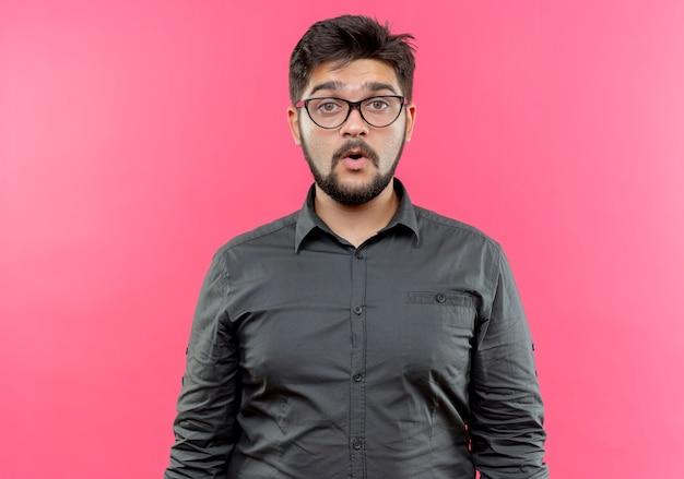 Beeindruckter junger geschäftsmann, der brillen trägt, die auf rosa wand lokalisiert werden