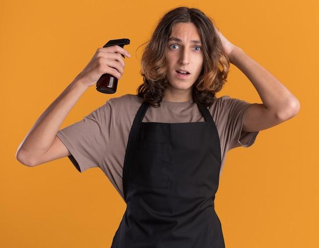 Beeindruckter junger gutaussehender friseur in uniform, der eine sprühflasche hält, die die hand auf dem kopf hält und nach vorne isoliert auf der orangefarbenen wand schaut