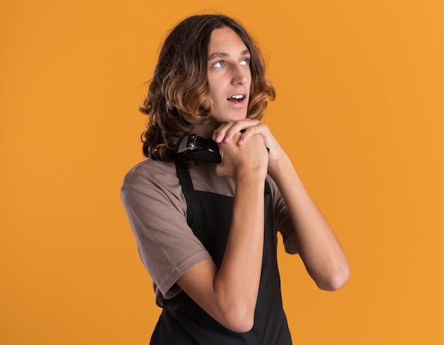 Beeindruckter junger gutaussehender friseur in uniform, der haarschneidemaschinen hält und die hände unter dem kinn zusammenhält und auf die seite isoliert auf der orangefarbenen wand mit kopierraum schaut